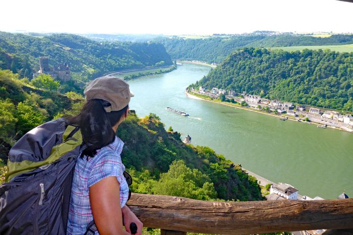 Hiker with view onto rhine River and castle Katz