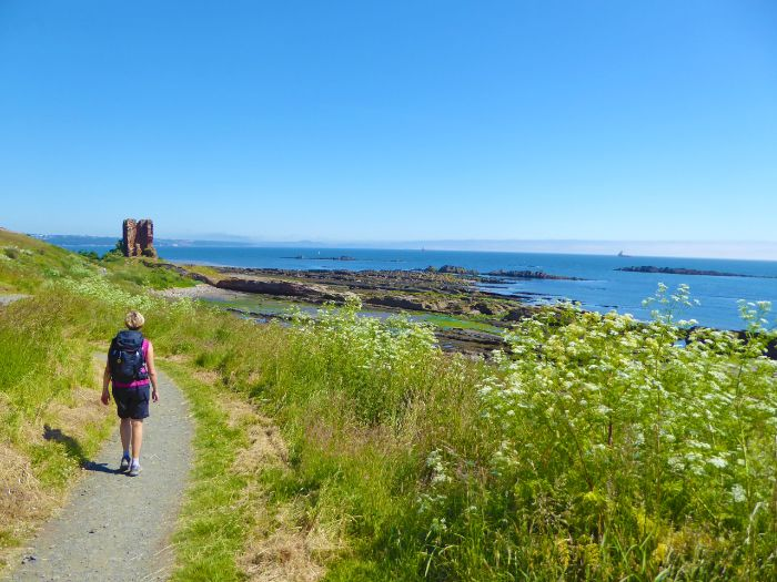 Panorama view on the coastal path with a hiker