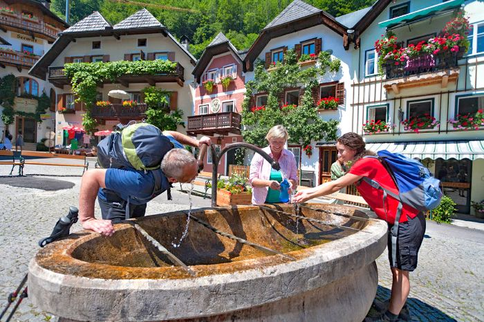 Hikers enjoy a refreshment at the village fountain of Hallstatt