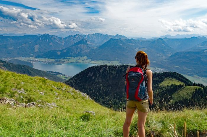 Hiker with view to lake Wolfgangsee and the alpine peaks of Salzkammergut
